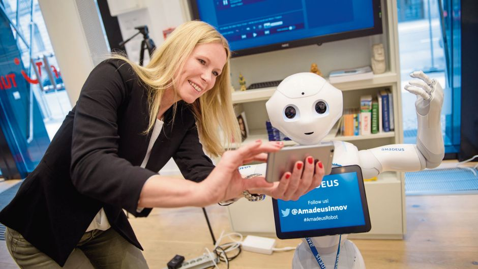 New technology is taking over tourism. Anja Braun (TUI Germany) takes a selfie with robot Pepper in the TUI Flagship Store in Berlin in 2017.
