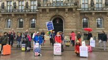Vor dem Hamburger Rathaus lassen sich die Touristiker auch nicht vom Regenwetter abschrecken: Sie stehen trotz des trüben Aprilwetters für ihre Sache ein.