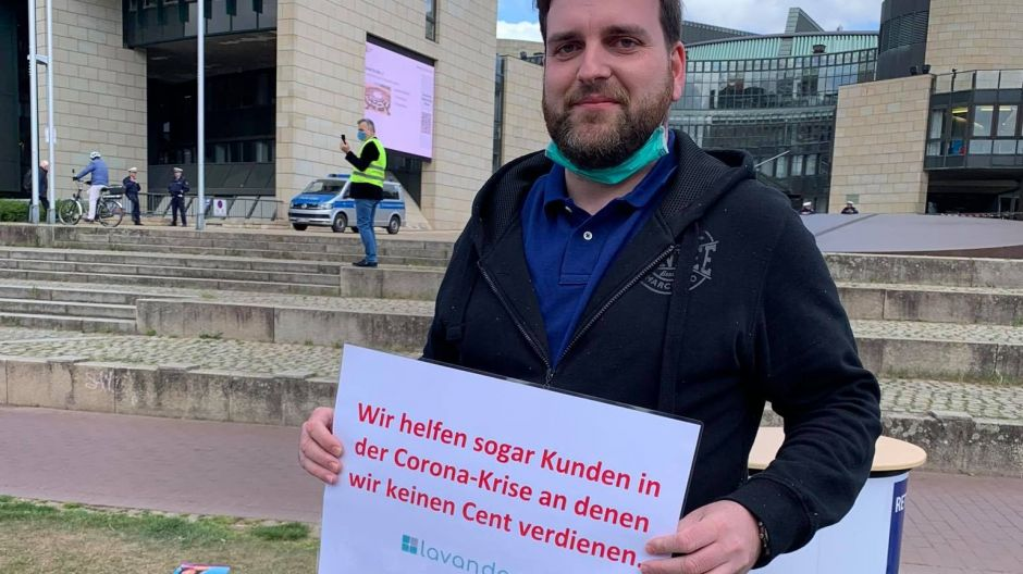 """During the Corona crisis, we even help clients who we do not earn a single cent from"": a protester in Dusseldorf."