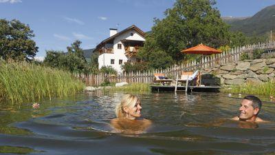 Kleine Betriebe, Ferien mit Abstand: Urlaub auf dem Bauernhof erfreut sich in Corona-Zeiten reger Nachfrage. Roter Hahn, die Landurlaub-Marke in Tirol, registriert zudem einen Trend zu mehr Komfort, Apartments statt Zimmern sowie immer mehr Paaren, die zum Beispiel die Landromantik im Naturbadeteich wie hier auf dem Frötscherhof in Brixen zu schätzen wissen